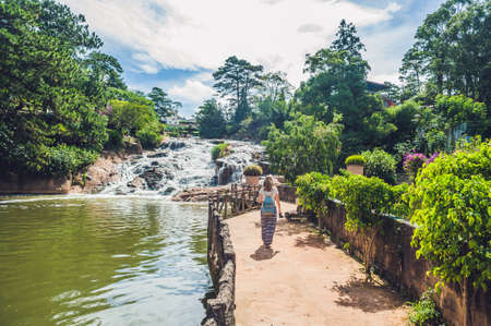 panoramas: Young woman on the background of Beautiful Camly waterfall In Da Lat city,