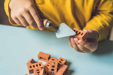 Close up of childs hands playing with real small clay bricks at the table. Toddler having fun and building out of real small clay bricks. Early learning. Developing toys. Construction concept.