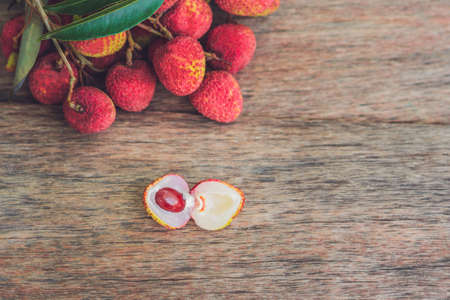Fresh litchi fruit on an old wooden background. Stock Photo