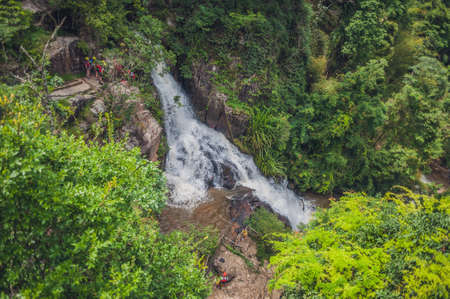 crampon: Climbers go down a cliff near a waterfall.