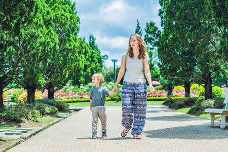 Mom and son are walking in the tropical park.