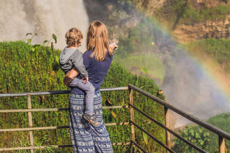 dalat: Mom and son on the background of Majestic landscape of Elephant waterfall in summer at Lam Dong Province, Dalat, Vietnam. Look at the rainbow. Stock Photo