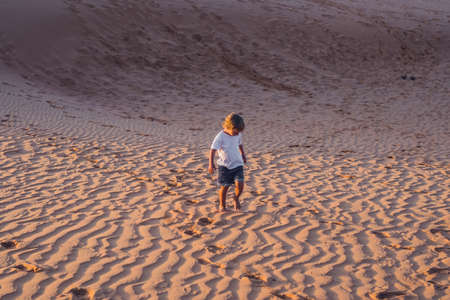 The boy runs around the red desert at dawn. Traveling in a fuss with children concept.