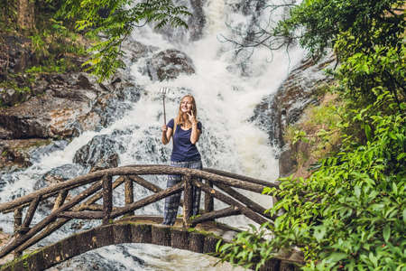 Excited female tourist making self portrait in front of the waterfall. Woman having a great vacation in Vietnam.