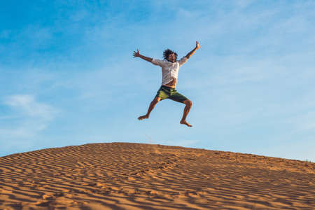 Beautiful young man jumping barefoot on sand in desert enjoying nature and the sun. Fun, joy and freedom.