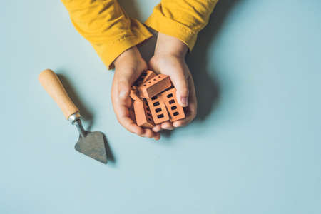 Close up of child's hands playing with real small clay bricks at the table. Toddler having fun and building out of real small clay bricks. Early learning. Developing toys. Construction concept.