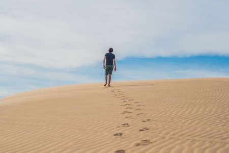 ne: A man is walking in the desert Vietnam, Mui Ne.