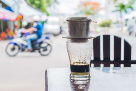 Vietnamese coffee in a street cafe on the background of a road.