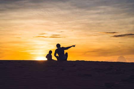 Vater und Sohn in der roten Wüste im Morgengrauen. Reisen mit Kindern Konzept.