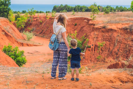 Mother and son travelers in red canyon near Mui Ne, southern Vietnam. Traveling with children concept. Stock Photo
