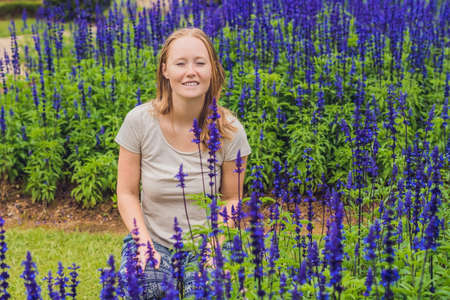 Young woman on the background of Blue salvia farinacea flowers blooming in the garden.
