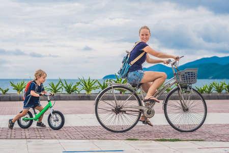 행복한 가족 자전거를 야외에서 타고 웃고. 엄마와 자전거에 아들과 균형 자전거. 스톡 콘텐츠
