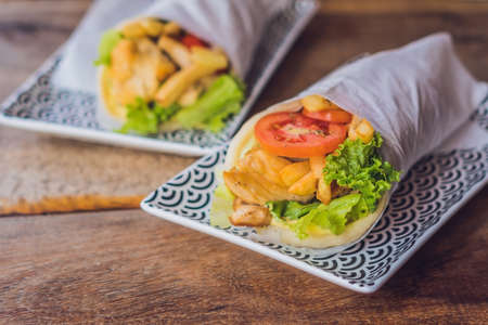breadbasket: Greek gyros wrapped in a pita bread on a wooden background. Greek cuisine concept.
