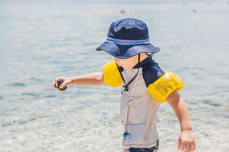 The boy enjoys the tropical sea and the beach.
