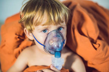 inhalation: Boy making inhalation with a nebulizer at home. Stock Photo