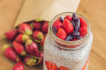 Healthy layered dessert with chia pudding, strawberry and honeysuckle in a mason jar on rustic background.