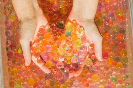 absorbent: Colored balls of water beads, hydrogel in in hands. Sensory experiences. Stock Photo