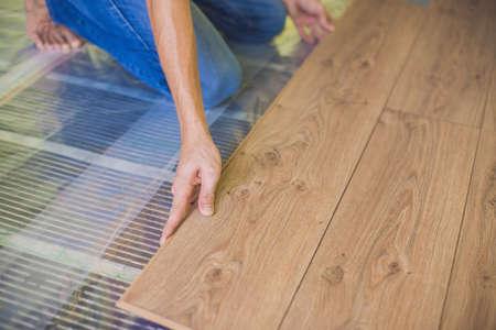 따뜻한 나무 바닥에 새로운 나무 라미네이트 바닥을 설치하는 사람 (남자). 라미네이트 바닥 아래의 적외선 바닥 난방 시스템 스톡 콘텐츠