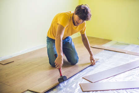 Man Installing New Wooden Laminate Flooring On A Warm Film Floor