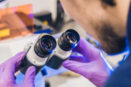 Scientist work on a confocal scanning microscope in a laboratory for biological samples investigation. Stock Photo