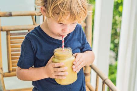 Boy holding a banana smoothie, proper nutrition concept.