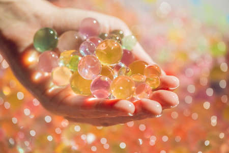 Colored balls of water beads, hydrogel in in hands. Sensory experiences. Stock Photo