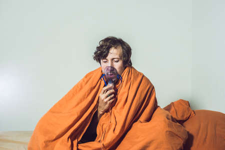 man with flu or cold symptoms making inhalation with nebulizer - medical inhalation therapy. Archivio Fotografico
