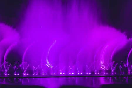 Multicolored dancing water jet fountain in the dark. Stock Photo