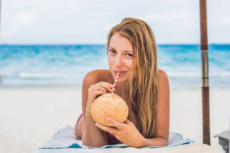 Young woman drinking coconut milk on Chaise-longue on beach. Dream scape Escape with beauty girl. The Benefits of Coconut Water.