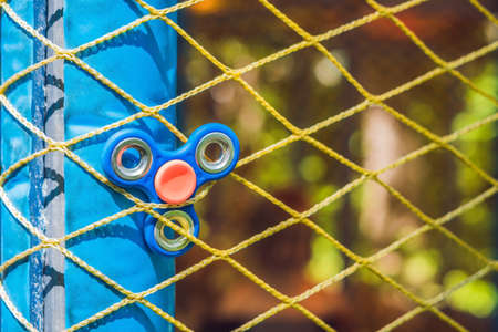 Finger spinner on the playground. Blurred background.