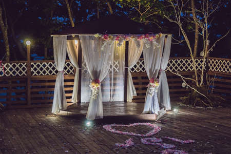 Night wedding ceremony. Decorations for wedding ceremony arch and lamps in the night forest.