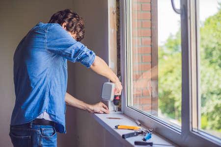 Man in a blue shirt does window installation. 版權商用圖片 - 83260462