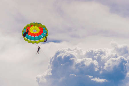 Young woman flies on a parachute among the clouds.