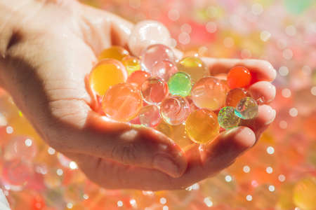 gel capsule: Colored balls of water beads, hydrogel in in hands. Sensory experiences. Stock Photo