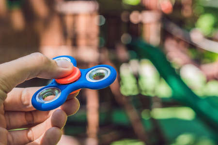 Boy playing with fidget spinner. Child spinning spinner on the playground. Blurred background. Stock Photo