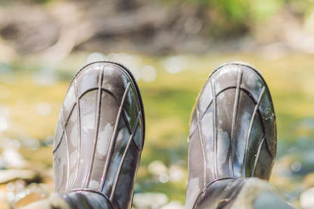 Man s foot in rubber boots. Rubber boots of the fisherman. Stock Photo