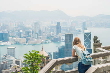 Young woman traveler at the peak of Victoria against the backdrop of Hong Kong. Stock Photo