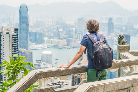 Young man traveler at the peak of Victoria against the backdrop of Hong Kong.
