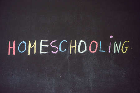 homeschooling: Homeschooling. Child pointing at word Homeschooling on a blackboard.