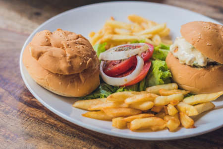 Greek food concept. Bun with chicken salad, french fries. Stock Photo
