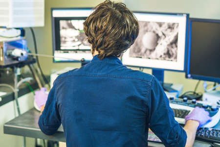 Scientist works at a electron microscope control pannel with two monitors in front of him.