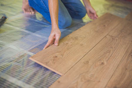 Man Installing New Wooden Laminate Flooring On A Warm Film Floor