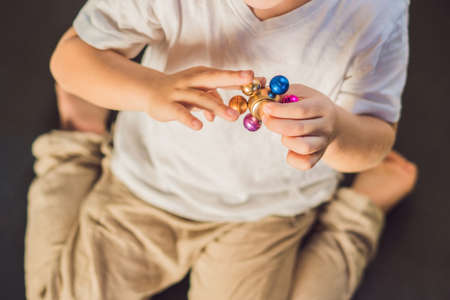 Young boy play with fidget spinner stress relieving toy. Stock Photo
