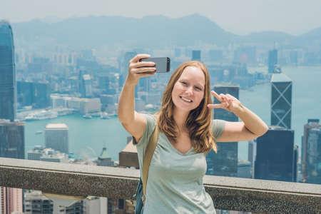 Hong Kong Victoria Peak-vrouw die selfie foto van het stokbeeld met smartphone nemen die van mening over de Haven van Victoria genieten. Kijkplatform op de top van Peak Tower, HK. Defocused achtergrond. Reis Azië concept. Stockfoto - 86162156