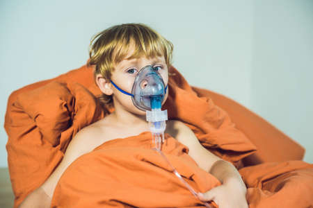 Boy making inhalation with a nebulizer at home. Stock Photo