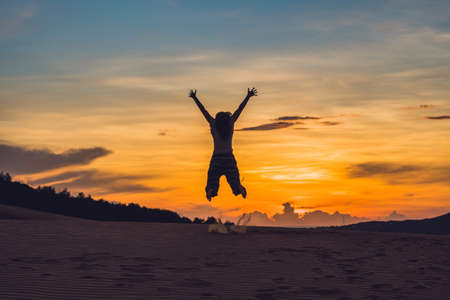 young woman in rad sandy desert at sunset or dawn Stock Photo
