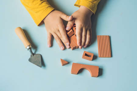 learning new skills: Close up of childs hands playing with real small clay bricks at the table. Toddler having fun and building out of real small clay bricks. Early learning. Developing toys. Construction concept.