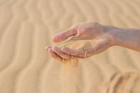 nails: Desert, sand puffs through the fingers of a mans hand.