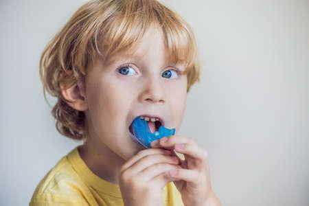 3 살짜리 소년이 입안의 호흡 습관을 조명하기 위해 근력 트레이너를 보여줍니다. 성장하는 치아를 균등하게하고 올바른 교합을 돕습니다. 혀의 위치