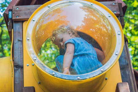 a Toddler girl playing on multi-colored playground.